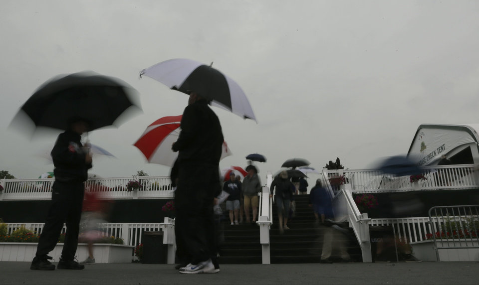 Photo - Spectators wait out a weather delay during the first round of the U.S. Open golf tournament at Merion Golf Club, Thursday, June 13, 2013, in Ardmore, Pa. (AP Photo/Morry Gash)