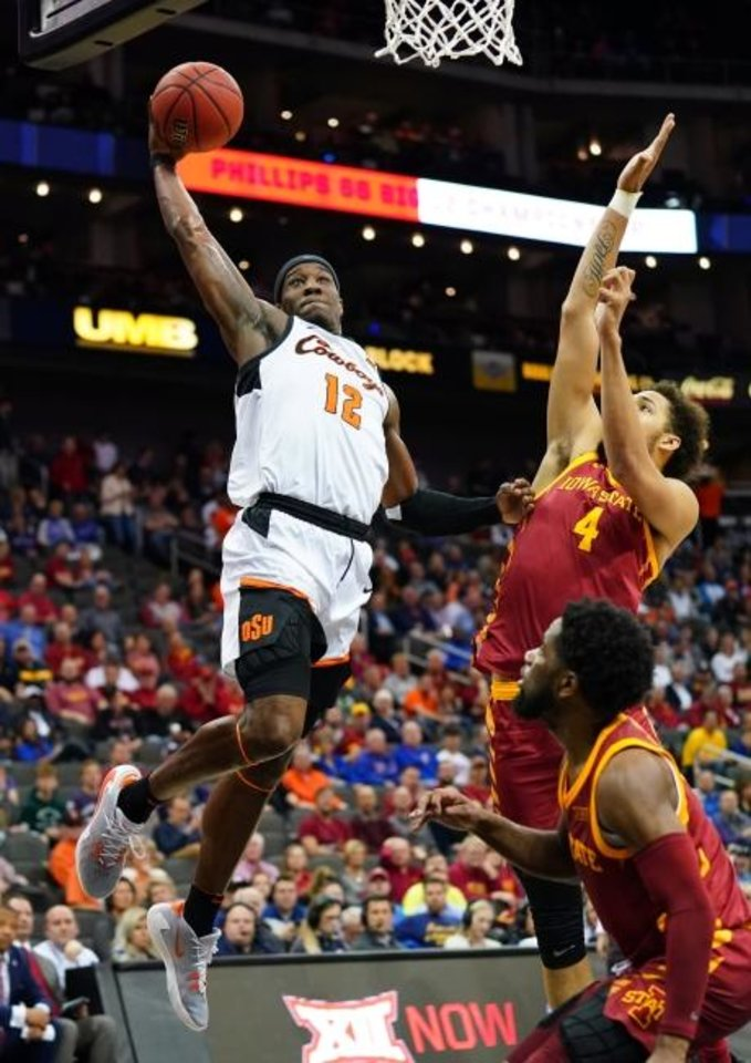 Photo -  Oklahoma State's Cameron McGriff, left, dunks against Iowa State's George Conditt IV, middle. and Tre Jackson on Wednesday in the Big 12 Tournament's opening game. [Jay Biggerstaff/USA TODAY Sports]