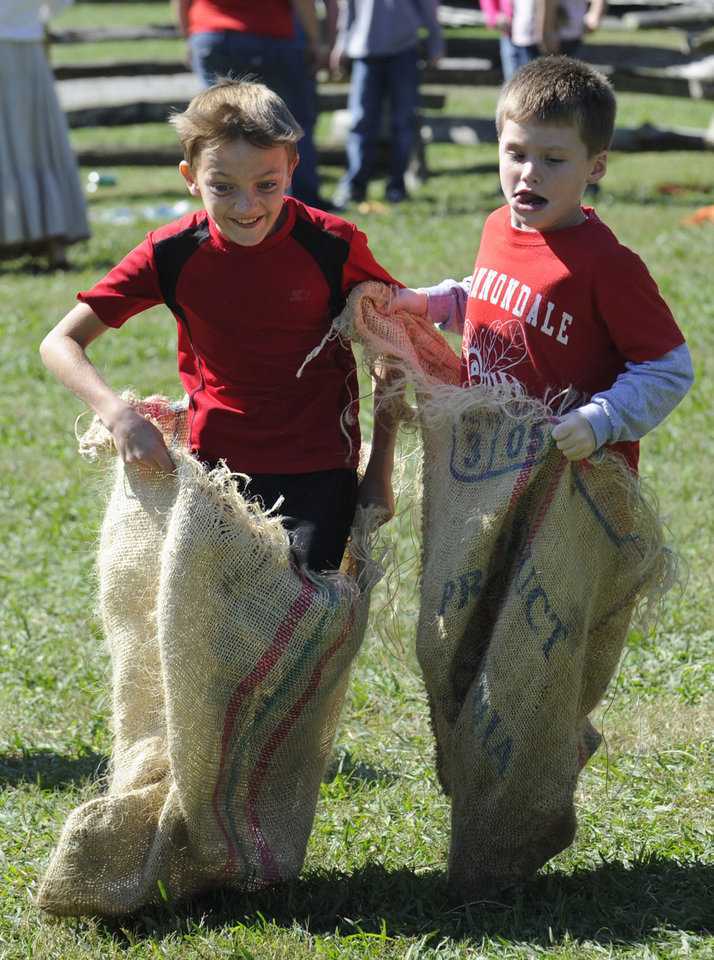Tyler Lemay, left, and Dylan McGhee compete in the sack race during the 33rd annual Tennessee Fall Homecoming at the Museum of Appalachia Thursday, Oct. 11, 2012, in Clinton, Tenn. The Museum of Appalachia is holding its 33rd Tennessee Fall Homecoming in Norris this weekend. (AP Photo/Knoxville News Sentinel, Amy Smotherman Burgess)