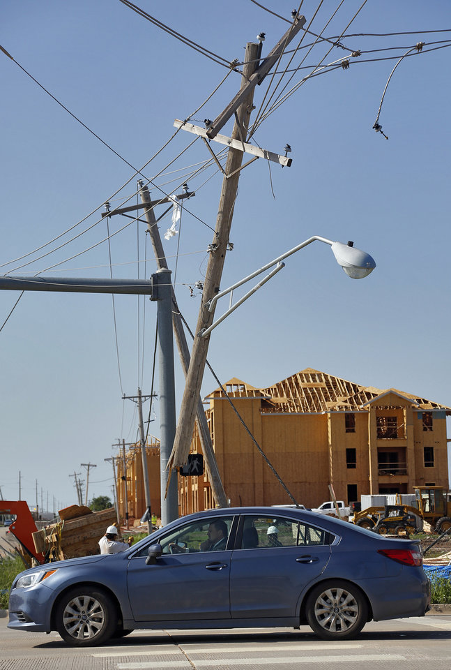 Photo - A power pole hangs above the intersection of NW 36th Ave. and Tecumseh Road in Norman, Okla. on Thursday, May 7, 2015.  Photo by Chris Landsberger, The Oklahoman