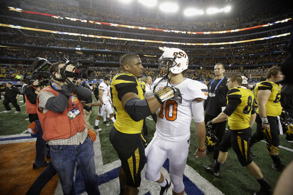 Photo - In this Jan. 3, 2014 photo, Missouri defensive lineman Michael Sam (52) and Oklahoma State quarterback Clint Chelf (10) greet each other on the field after the Cotton Bowl NCAA college football game, in Arlington, Texas. Missouri's All-America defensive end came out to the entire country Sunday, Feb. 9, 2014, and could become the first openly homosexual player in the NFL. (AP Photo/Tim Sharp)