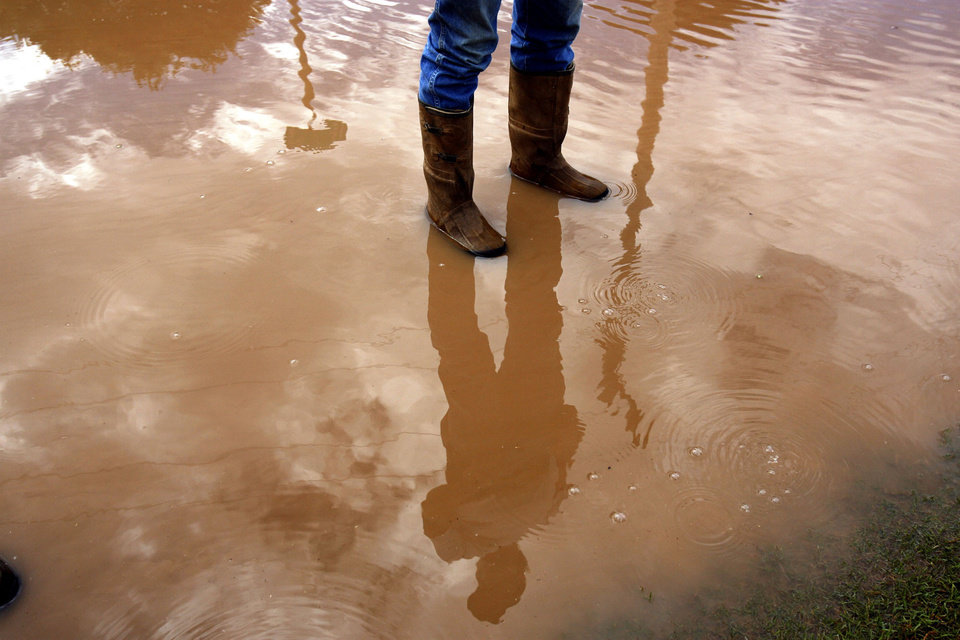 Monty Ferrell is reflected in flood waters in Burlington, Okla., Saturday, September 13, 2008. The town flooded after heavy rains and a breach in a land dike. BY SARAH PHIPPS, THE OKLAHOMAN.