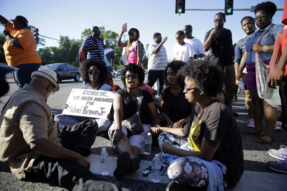 Photo - A small group of protesters block traffic by sitting in the street before police in riot gear arrived in Ferguson, Mo. on Wednesday, Aug. 13, 2014. On Saturday, Aug. 9, 2014, a white police officer fatally shot Michael Brown, an unarmed black teenager in the St. Louis suburb. (AP Photo/Jeff Roberson)