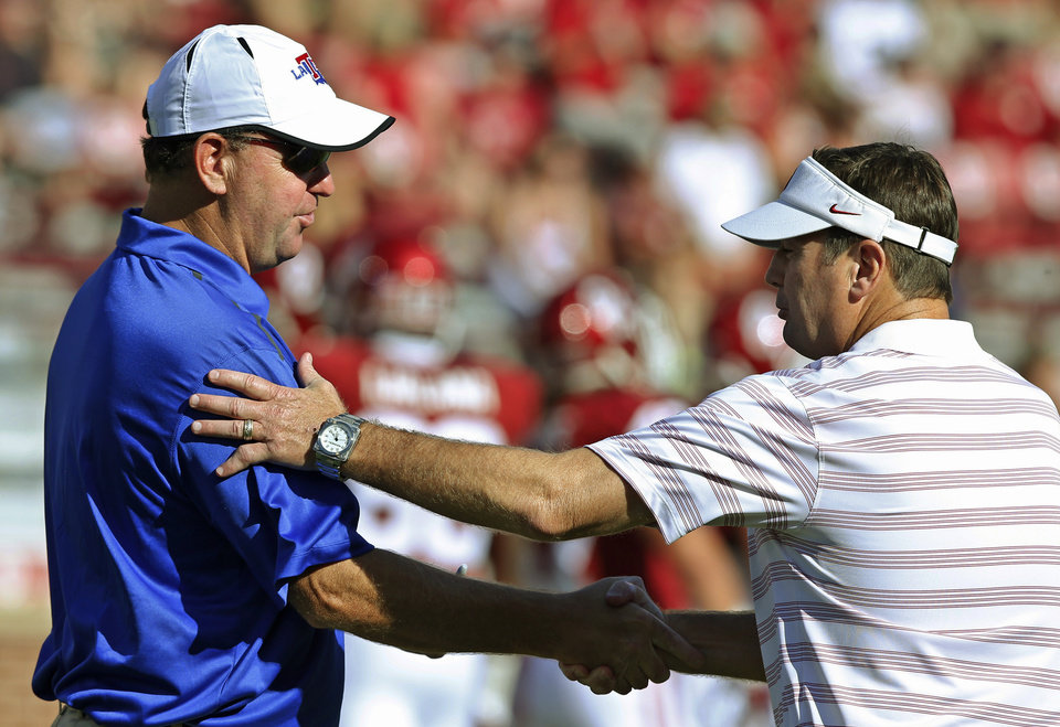 Photo - Louisiana Tech coach Skip Holtz, left, and Oklahoma coach Bob Stoops shake hands before an NCAA college football game in Norman, Okla., Saturday, Aug. 30, 2014. (AP Photo/Sue Ogrocki)
