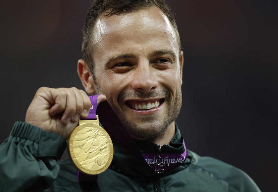 "FILE - In this Saturday, Sept. 8, 2012, file photo, Gold medalist South Africa's Oscar Pistorius poses with his medal during the ceremony after winning the men's 400 meters T44 category final during the athletics competition at the 2012 Paralympics, in London. Olympic sprinter Oscar Pistorius has been arrested after a 30-year-old woman was shot dead at his home in South Africa. Police say Pistorius, a double-amputee known as ""Blade Runner,"" was taken into custody after the shooting early Thursday,  Feb. 14, 2013,  at his home in a gated complex in the country's capital.  (AP Photo/Matt Dunham, File)"