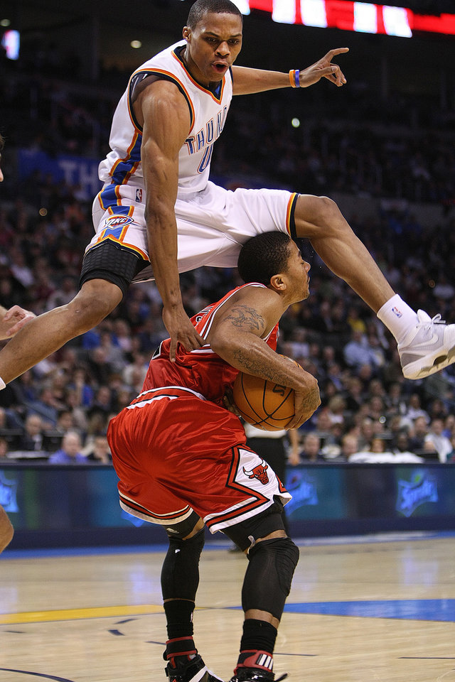 Photo - OKLAHOMA CITY THUNDER / CHICAGO BULLS / NBA BASKETBALL  Oklahoma City Thunder guard Russell Westbrook leaps over Chicago's Derrick Rose during the Thunder - Bulls game January 27, 2010 in the Ford Center in Oklahoma City.    BY HUGH SCOTT, THE OKLAHOMAN ORG XMIT: KOD