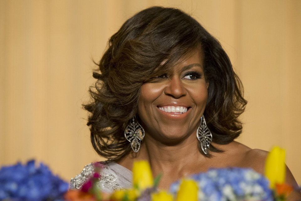First lady Michelle Obama laughs while listening to President Obama's speech during the White House Correspondents' Association (WHCA) Dinner at the Washington Hilton Hotel, Saturday, May 3, 2014, in Washington. (AP Photo/Jacquelyn Martin)