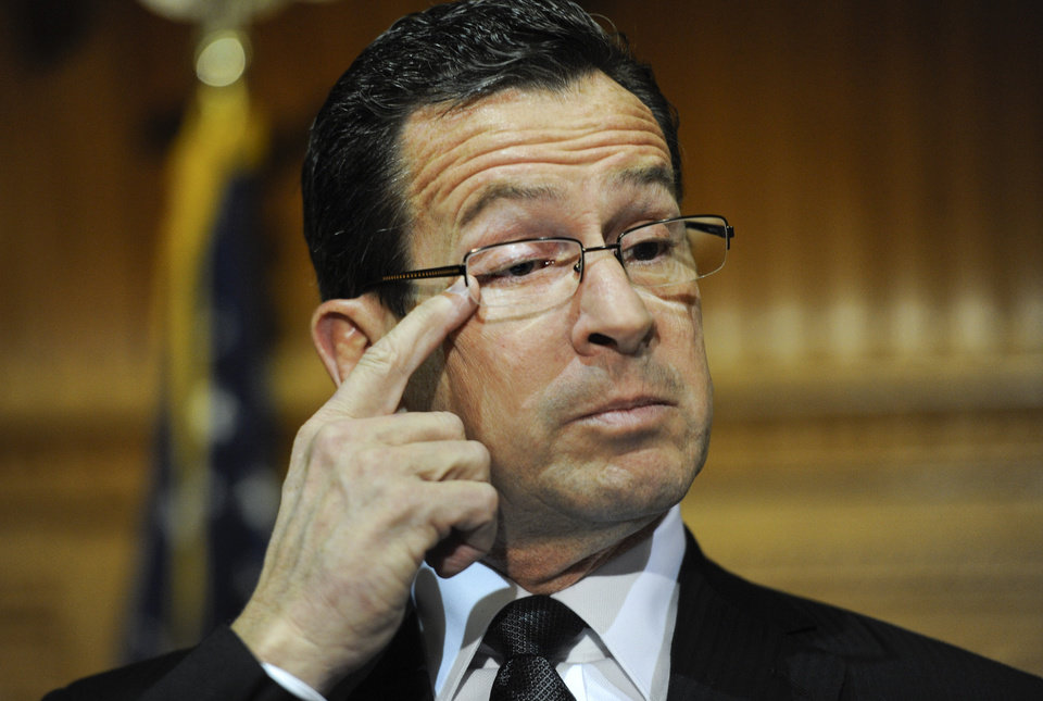 Photo - Connecticut Gov. Dannel P. Malloy wipes away a tear as he recalls how and why he decided to tell the families of the Sandy Hook Elementary School shooting that their loved ones were dead during a news conference at the Capitol in Hartford, Conn., Monday, Dec. 17, 2012. (AP Photo/Jessica Hill) ORG XMIT: CTJH103