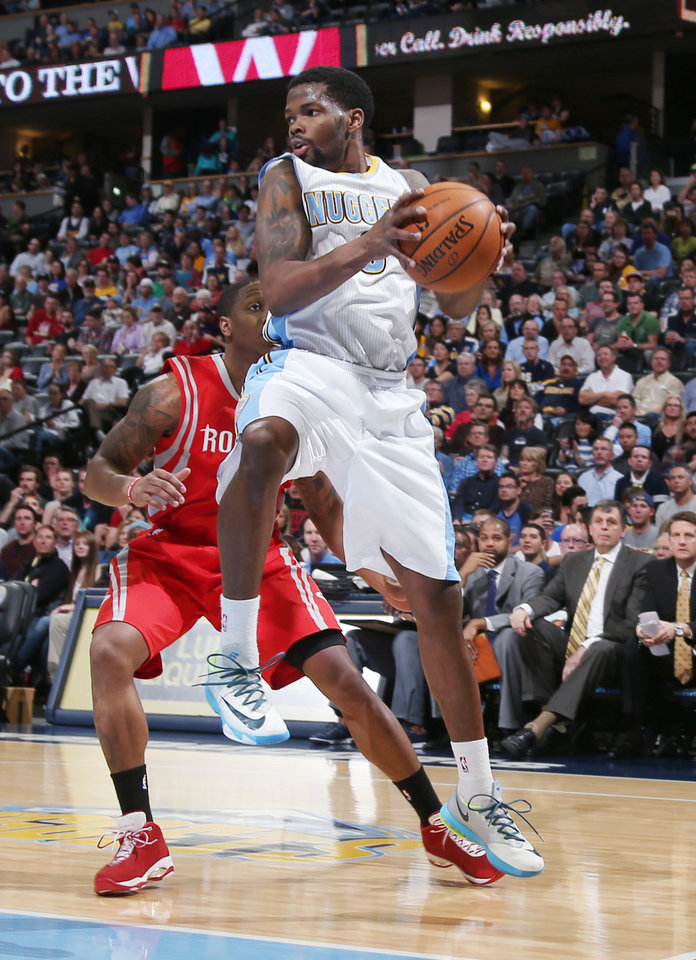 Photo - Denver Nuggets guard Aaron Brooks, front, pulls in a loose ball in front of Houston Rockets guard Isaiah Canaan in the first quarter of an NBA basketball game in Denver on Wednesday, April 9, 2014. (AP Photo/David Zalubowski)
