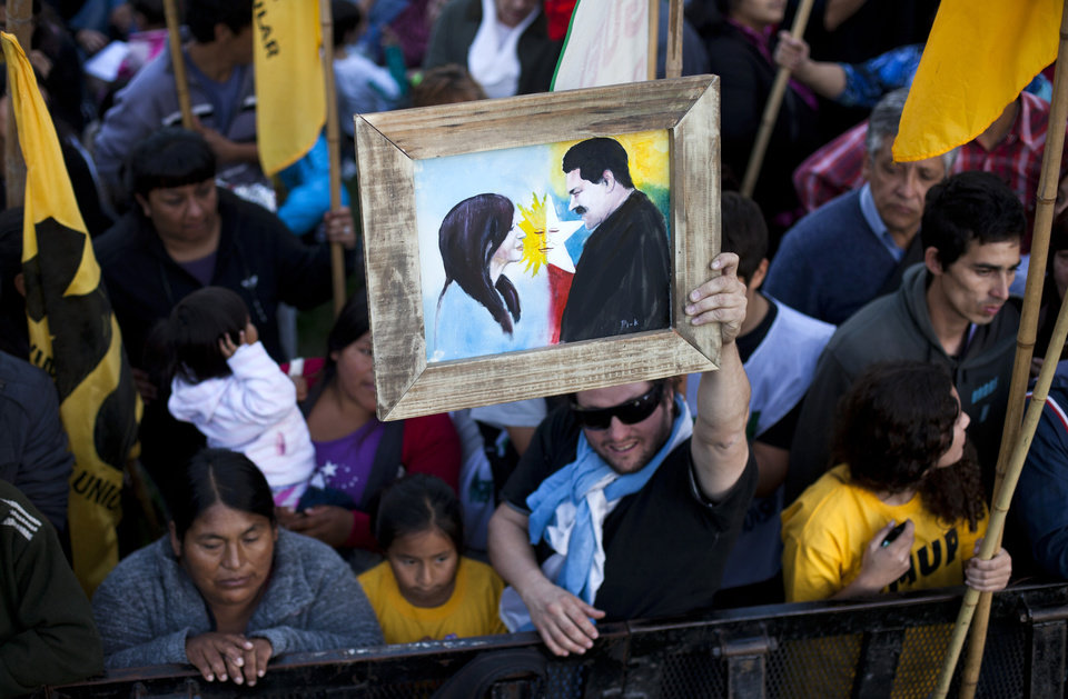 Photo - An activist shows a painting of Argentina's President Cristina Fernandez and Venezuela's President Nicolas Maduro during a rally with Maduro in Buenos Aires, Argentina, Wednesday, May 8, 2013. Maduro said their two countries are more closely aligned than ever despite the deaths of Venezuelan President Hugo Chavez and of Nestor Kirchner, Fernandez's husband who preceded her in the presidency. (AP Photo/Victor R. Caivano)