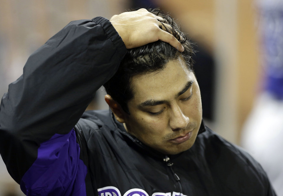 Photo - Colorado Rockies starting pitcher Jorge De La Rosa puts his hand on his head in the dugout after the Miami Marlins scored three runs in the fifth inning after he was relieved during an opening day baseball game, Monday, March 31, 2014, in Miami. (AP Photo/Lynne Sladky)