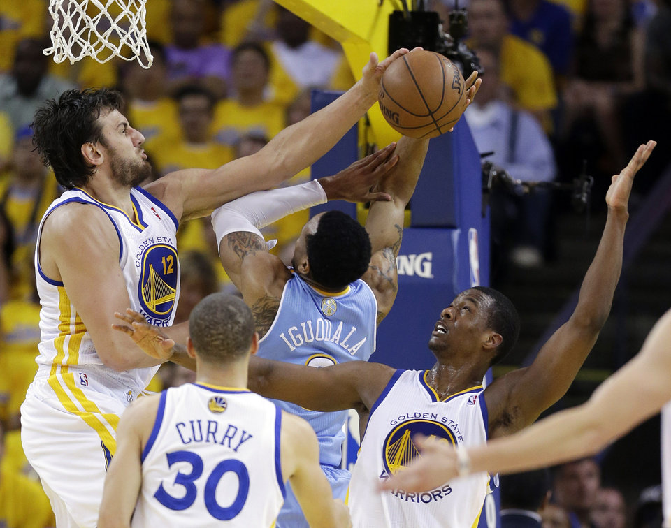 Photo - Golden State Warriors' Andrew Bogut, top left, blocks a shot by Denver Nuggets' Andre Iguodala, center, as Warriors' Harrison Barnes, right, watches during the first half of Game 6 in a first-round NBA basketball playoff series in Oakland, Calif., Thursday, May 2, 2013. (AP Photo/Marcio Jose Sanchez)