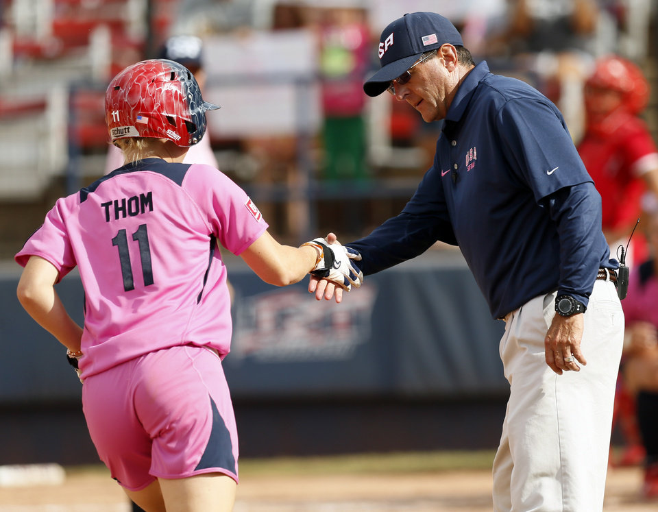 Photo - United States head coach Ken Eriksen shakes the hand of Taylor Thom (11) as she passes third base after hitting a home run in the fifth inning during a game in the World Cup of Softball between the USA and Puerto Rico at ASA Hall of Fame Stadium in Oklahoma City, Sunday, July 14, 2013. Team USA won, 10-3 in five innings. Photo by Nate Billings, The Oklahoman