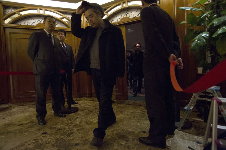 Photo - A man walks out of a room reserved for relatives of Chinese passengers aboard missing Malaysia Airlines flight MH370 at a hotel in Beijing, China, Saturday, March 15, 2014. Investigators have concluded that one or more people with significant flying experience hijacked the missing Malaysia Airlines jet, switched off communication devices and steered it off-course, a Malaysian government official involved in the investigation said Saturday. (AP Photo/Ng Han Guan)