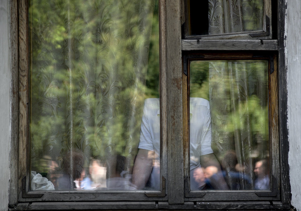 Photo - In this picture taken on Tuesday, May 20, 2014, a man watches from the headquarters of a coal mine outside Donetsk, Ukraine, as employees, reflected in the window, gather outside the building, refusing to take part in a management initiated rally against pro-Russian separatists. In the roiling debate over eastern Ukraine, where pro-Russian separatist attacks have turned increasingly bloody, neither the country's richest man nor some of his dirt-poor compatriots have much time for patriotism, ethnic feuding or political parties.  (AP Photo/Vadim Ghirda)