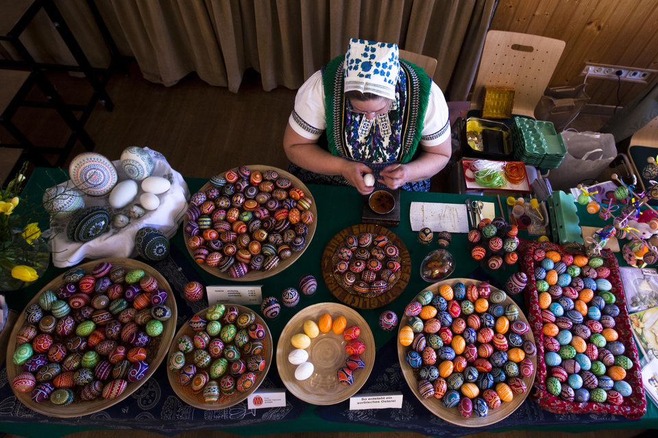 Photo - FILE - Kerstin Hanusch, a  Sorb woman,  paints an Easter egg  at a  market in Schleife, about 160 kilometers (100 miles) south-east of Berlin, on Saturday, March 24, 2012.  A tiny Slavic minority in Germany is keeping alive a long and intricate tradition of hand-painting Easter eggs _ with the help of feathers and wax. Shortly after Christmas every year, Karin Hannusch gets to work decorating up to 600 eggs for the annual Easter market in Schleife, a center of the small Sorbian community. (AP Photo/Markus Schreiber)