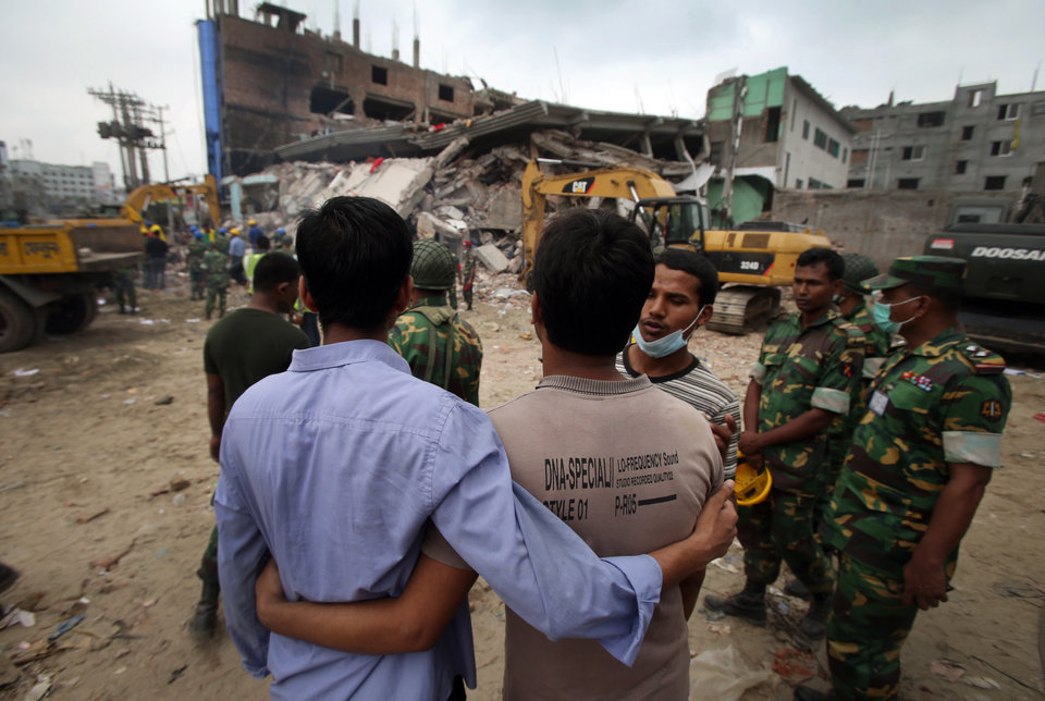 Grieving onlookers comfort each other while workers toil in a collapsed garment factory building on Tuesday, April 30, 2013 in Savar, near Dhaka, Bangladesh. Emergency workers hauling large concrete slabs from the collapsed eight-story building said Tuesday they expect to find many dead bodies when they reach the ground floor. (AP Photo/Wong Maye-E)