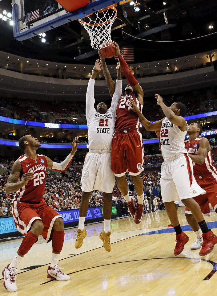 Photo - Oklahoma's Romero Osby (24) grabs a rebound against San Diego State's Jamaal Franklin (21) next to Chase Tapley (22) and Oklahoma's Amath M'Baye (22) during a game between the University of Oklahoma and San Diego State in the second round of the NCAA men's college basketball tournament at the Wells Fargo Center in Philadelphia, Friday, March 22, 2013. San Diego State beat OU, 70-55. Photo by Nate Billings, The Oklahoman
