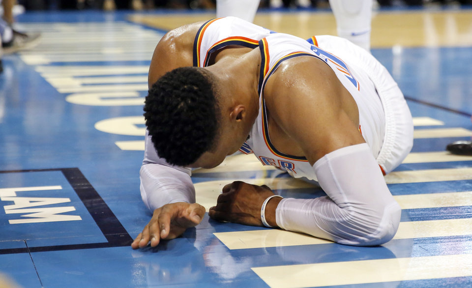 Photo - Oklahoma City's Russell Westbrook (0) slowly tries to sit up after being injured in the third quarter during an NBA basketball game between the Oklahoma City Thunder and the New Orleans Pelicans at Chesapeake Energy Arena in Oklahoma City, Monday, Nov. 5, 2018. Oklahoma City won 122-116. Photo by Nate Billings, The Oklahoman