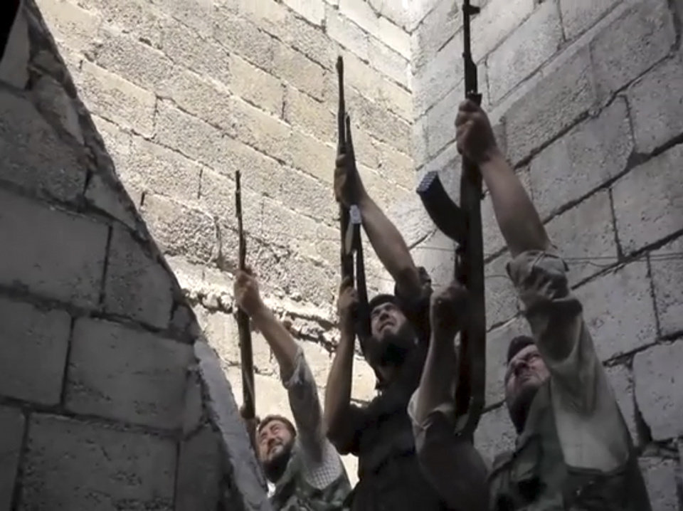 Photo -   In this image made from video and accessed Saturday, Sept. 1, 2012, Free Syrian Army fighters raise their weapons during fighting with the Syrian Army in Aleppo, Syria. Syrian troops bombarded the northern city of Aleppo Saturday with warplanes and mortar shells as soldiers clashed with rebels in different parts of Syria's largest city, activists said. The Britain-based Syrian Observatory for Human Rights said the clashes were concentrated in several tense neighborhoods where some buildings were damaged and a number of people were wounded. (AP Photo/Robert King via AP video)