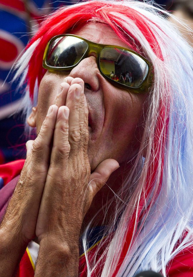 Photo - A Costa Rica soccer fan watches his team's Brazil World Cup round of 16 game with Greece by telecast at a public square in San Jose, Costa Rica, Sunday, June 29, 2014. Costa Rica won in a penalty shootout 5-3 after the match ended 1-1 following extra time. (AP Photo/Esteban Felix)