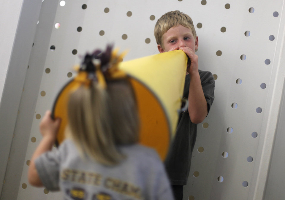 Photo - Robert Barnett, 5, and his sister Aislin, 2, of Kingfisher, play with a megaphone before a high school football game between Heritage Hall and Clinton in Oklahoma City, Friday, Sept. 7, 2012.  Photo by Garett Fisbeck, The Oklahoman