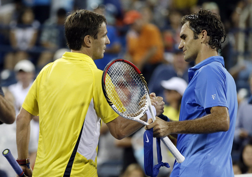 Tommy Robredo, of Spain, greets Roger Federer, of Switzerland, after winning their fourth round match in straight sets at the 2013 U.S. Open tennis tournament, Monday, Sept. 2, 2013, in New York. (AP Photo/Darron Cummings)