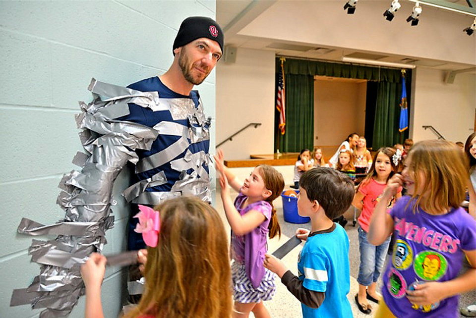"Greg Waggoner, a physical education teacher at Wayland Bonds Elementary School, gets duct-taped to a wall by students who contributed to a ""Pennies for Patients"" drive that benefits the Leukemia & Lymphoma Society. The charity, supported by schools across the country, is designed to instill compassion and teach the value of helping others. Donations pay for blood cancer research and patient aid programs.  Photo by Steve Olafson, for The Oklahoman"