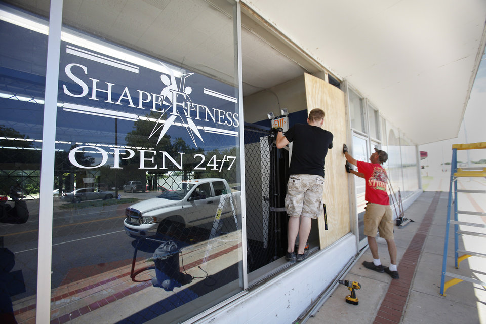 Photo -  Geoff Hampton and Larry Copeland board up a window at Shapes Fitness center that was broken in an early morning earthquake in Harrah on Tuesday. Photo by David McDaniel, The Oklahoman   David McDaniel