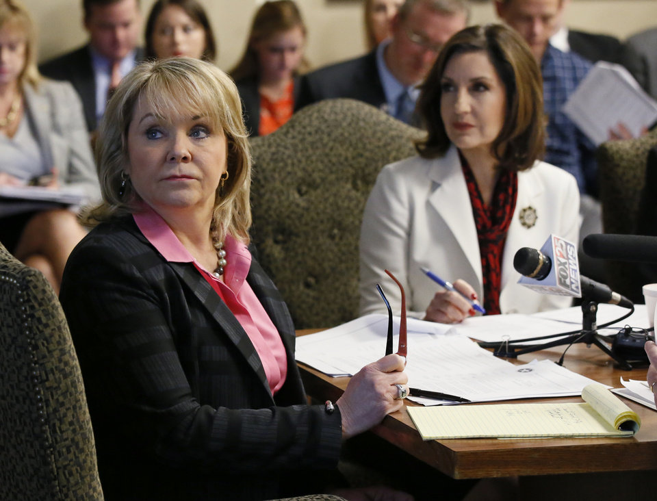 Photo -  Oklahoma Gov. Mary Fallin, left, and Joy Hofmeister, state superintendent of schools, listen to a presentation Tuesday at a Board of Equalization meeting. [AP Photo]