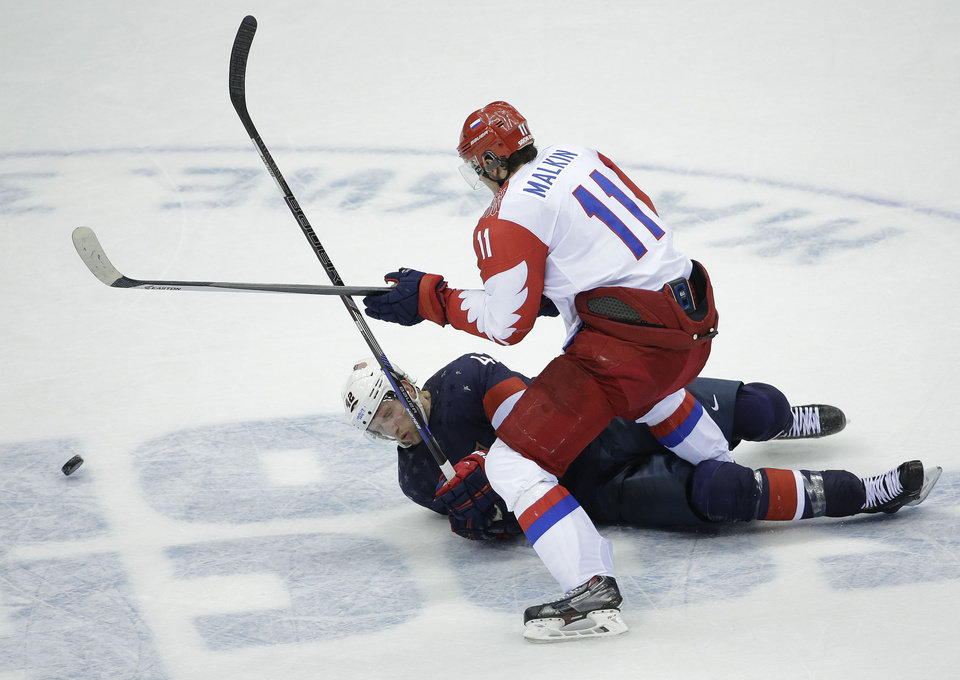 Photo - USA forward David Backes is knocked down by Russia forward Yevgeni Malkin in the third period of a men's ice hockey game at the 2014 Winter Olympics, Saturday, Feb. 15, 2014, in Sochi, Russia. (AP Photo/David J. Phillip )