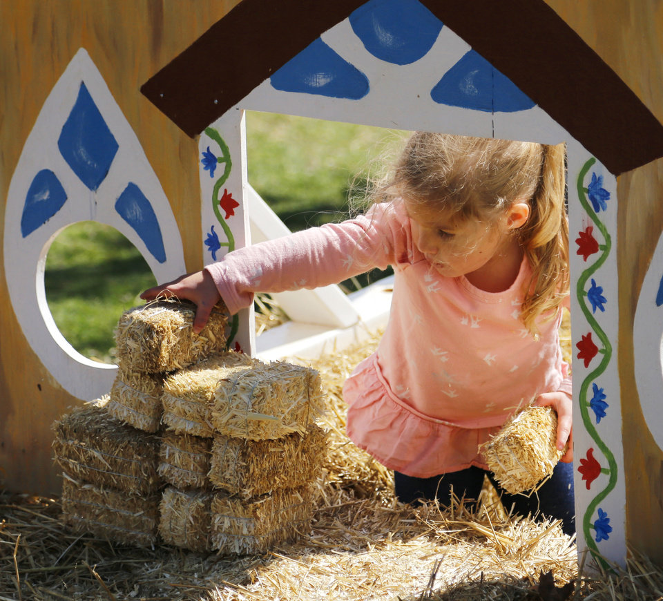 Photo -  Avery Graves, 3, Norman, stacks hay bricks at the Little Village during opening day at Pumpkinville. [Photo by Doug Hoke, The Oklahoman]