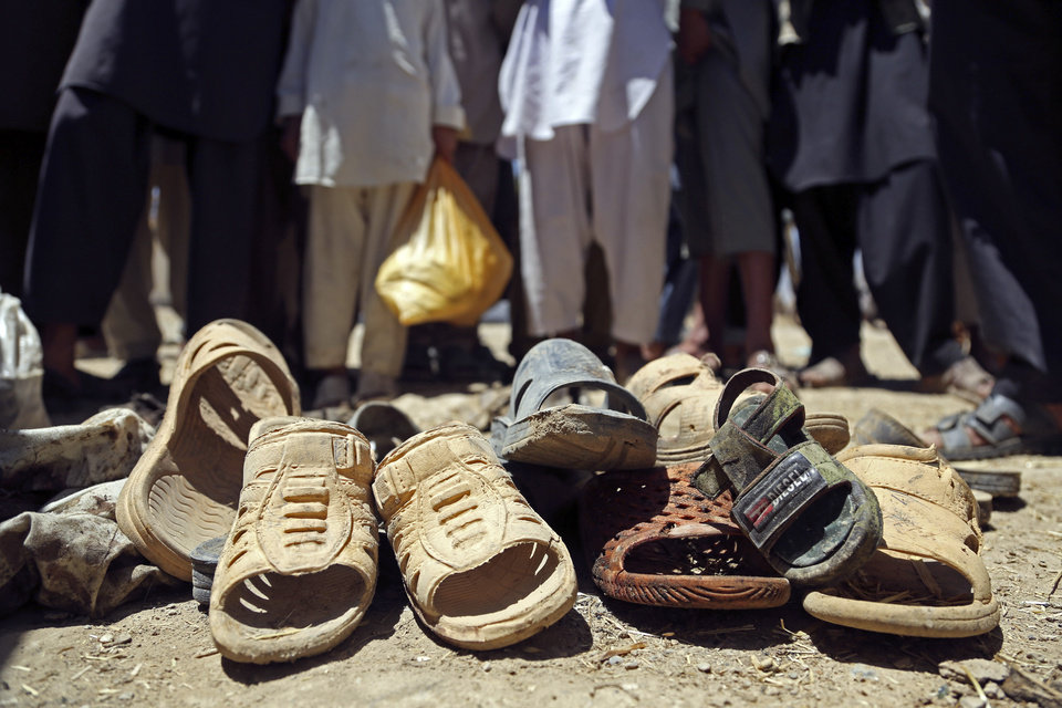 Photo - Afghans look at shoes that remain at the scene of a suicide attack in Parwan province in eastern Afghanistan, Tuesday, July 8, 2014. An Afghan official says that at least 16 people, including four Czech soldiers, were killed Tuesday in a suicide attack near a clinic in eastern Afghanistan. A provincial spokesman says the others killed are at least 10 civilians and two police officers. The Taliban claimed responsibility for the attack in a statement sent to the media. The violence came as Afghanistan was mired in an electoral crisis after one of the candidates in the presidential elections, Abdullah Abdullah, refused to accept any results until millions of ballots are audited for fraud. (AP Photo/Rahmat Gul)