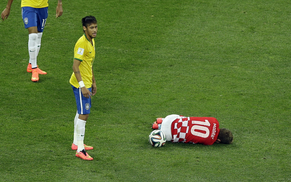 Photo - Croatia's Luka Modric, right, sits on the ground after being fouled by Brazil's Neymar, left, during the group A World Cup soccer match between Brazil and Croatia, the opening game of the tournament, in the Itaquerao Stadium in Sao Paulo, Brazil, Thursday, June 12, 2014. (AP Photo/Thanassis Stavrakis)