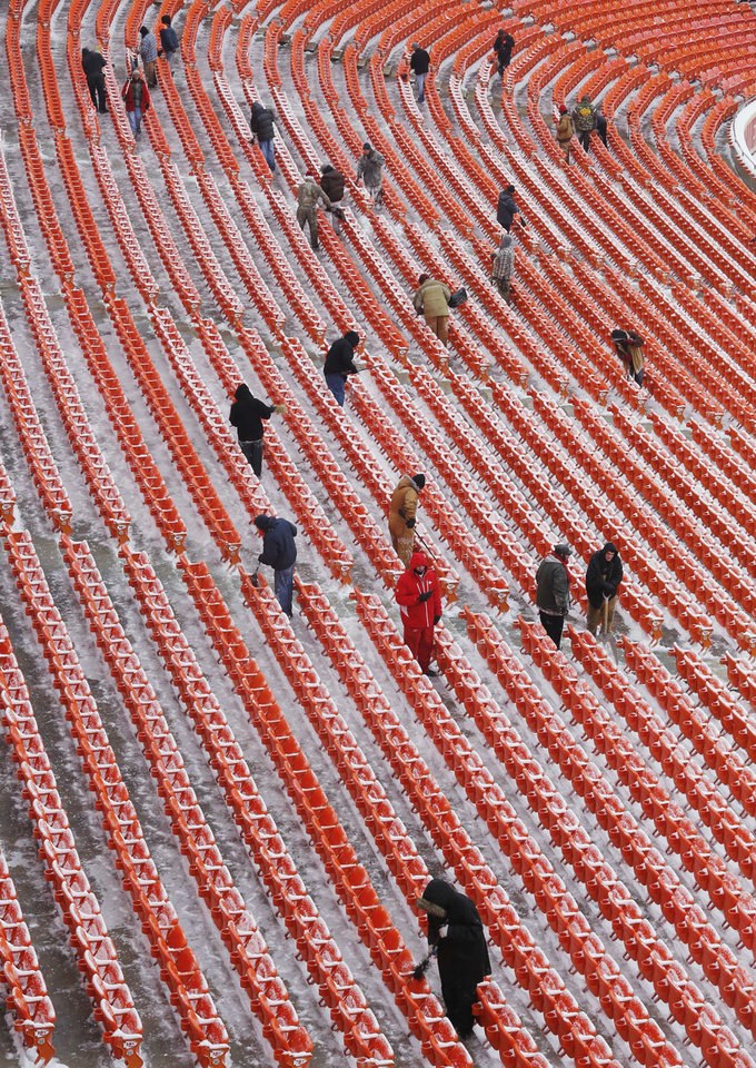 Photo - Workers clear snow from aisles and seats before an NFL football game between the Indianapolis Colts and Kansas City Chiefs at Arrowhead Stadium in Kansas City, Mo., Sunday, Dec. 22, 2013. (AP Photo/Orlin Wagner)