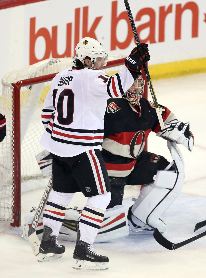 Photo - Chicago Blackhawks' Patrick Sharp (10) celebrates a goal as Ottawa Senators goaltender Craig Anderson (41) looks on during second-period NHL hockey game action in Ottawa, Ontario, Friday, March 28, 2014. (AP Photo/The Canadian Press, Fred Chartrand)