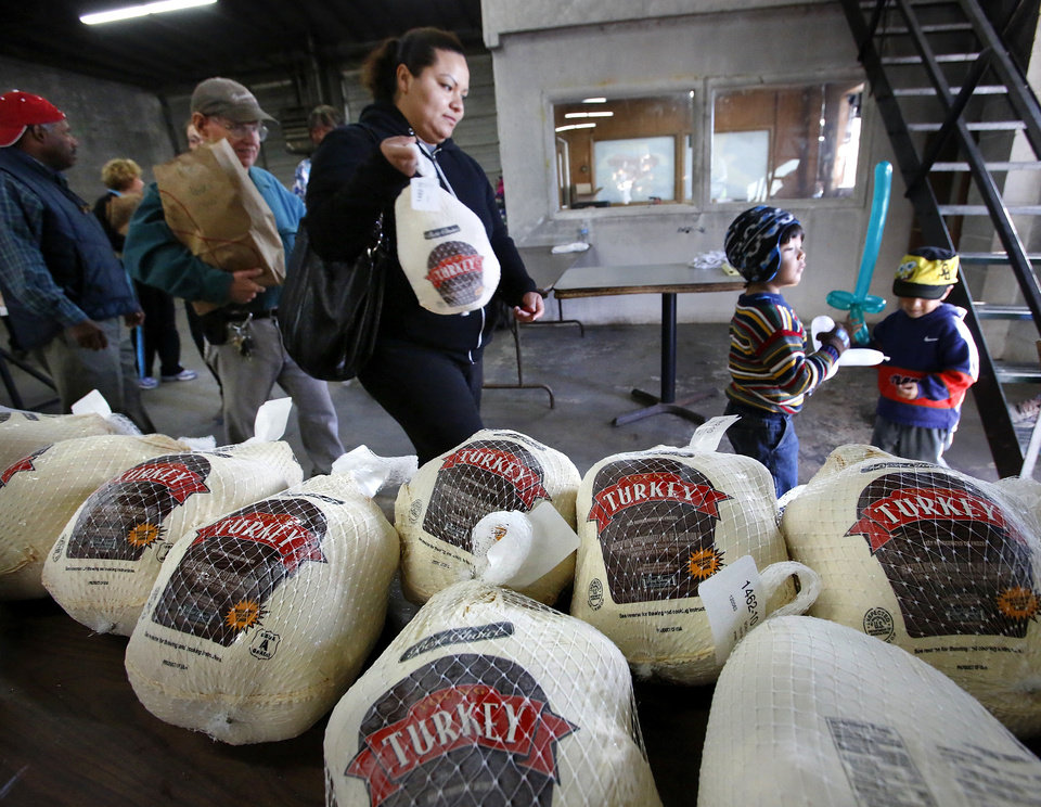 Photo - A woman and two children leave after picking up a Thanksgiving turkey and food basket on Nov. 19, 2012 at the Jesus House.   Jim Beckel - THE OKLAHOMAN