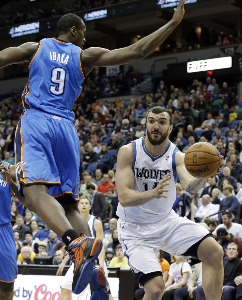 Minnesota Timberwolves\' Nikola Pekovic, right, of Montenegro, passes the ball under Oklahoma City Thunder\'s Serge Ibaka, of Congo, in the first quarter of an NBA basketball game, Friday, March 29, 2013, in Minneapolis. (AP Photo/Jim Mone) ORG XMIT: MNJM104