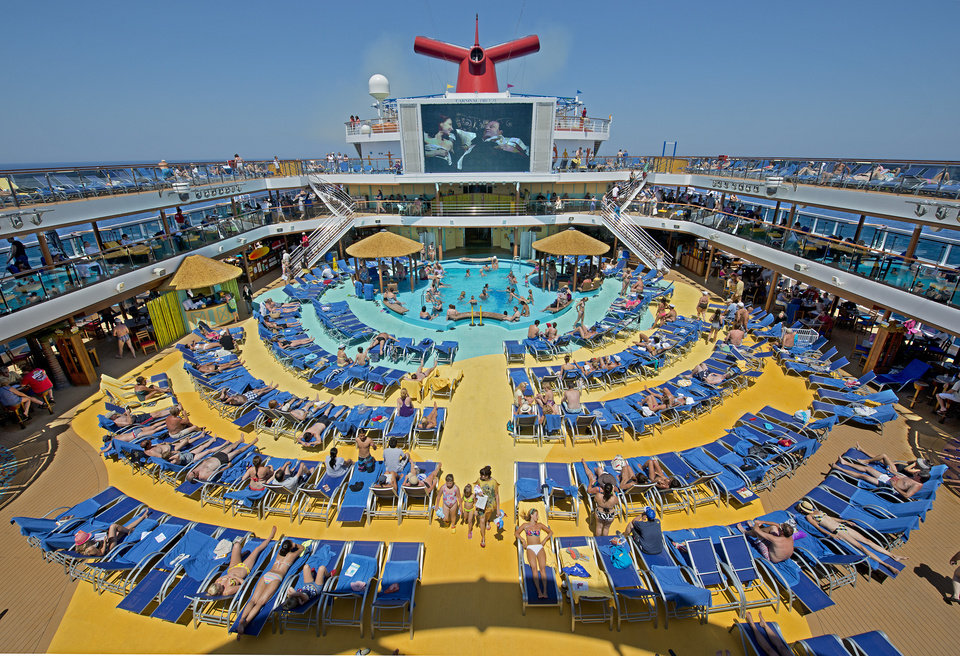 "Photo - In this June 23, 2012 photo provided by Carnival Cruise Lines, vacationers aboard the Carnival Breeze enjoy sunbathing at sea while viewing a movie at the Carnival's Seaside Theatre, a lido deck poolside 270-square-foot LED screen offering concerts, sporting events and other programming throughout the day as well as nightly ""Dive In Movies. (AP Photo/Carnival Cruise Lines, Andy Newman)"