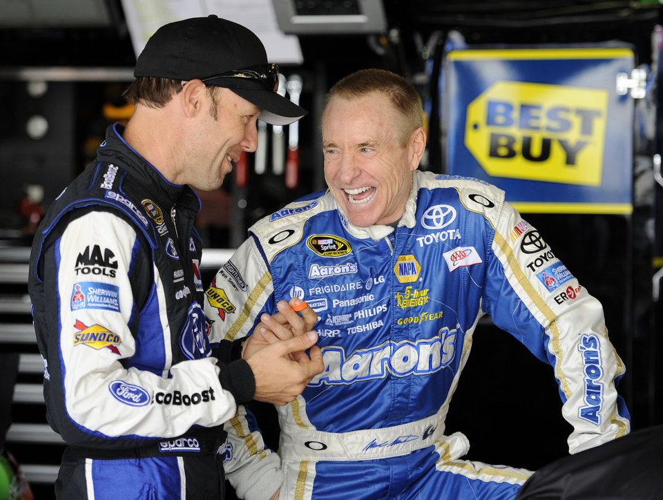 Driver Mark Martin, right, laughs with Matt Kenseth, left, in the garage area before practice for the AAA 400 NASCAR Sprint Cup Series auto race, Friday, Sept. 28, 2012, in Dover, Del. (AP Photo/Nick Wass)