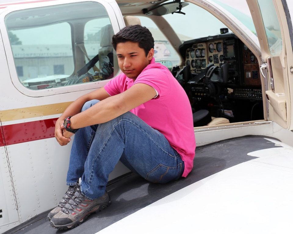 Photo - In this July 2014 photo provided by The Citizens Foundation 17-year-old Haris Suleman sits on the wing of his single-engine airplane in Lahore, Pakistan, on his around-the-world flight. The body of the Plainfield, Indiana teen was recovered after his single-engine plane crashed Tuesday, July 22, 2014 shortly after taking off from Pago Pago in American Samoa. Crews were still searching for his father, 58-year-old Babar Suleman, who was flying with him. (AP Photo/Courtesy The Citizens Foundation)