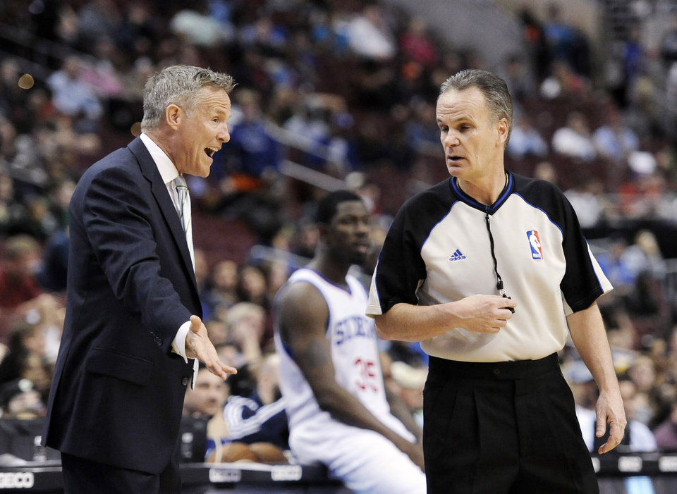 Photo - Philadelphia 76ers head coach Brett Brown argues a with official Mike Callahan during the second half of an NBA basketball game on Monday, April 14, 2014, in Philadelphia. The 76ers won 113-108. (AP Photo/Michael Perez)