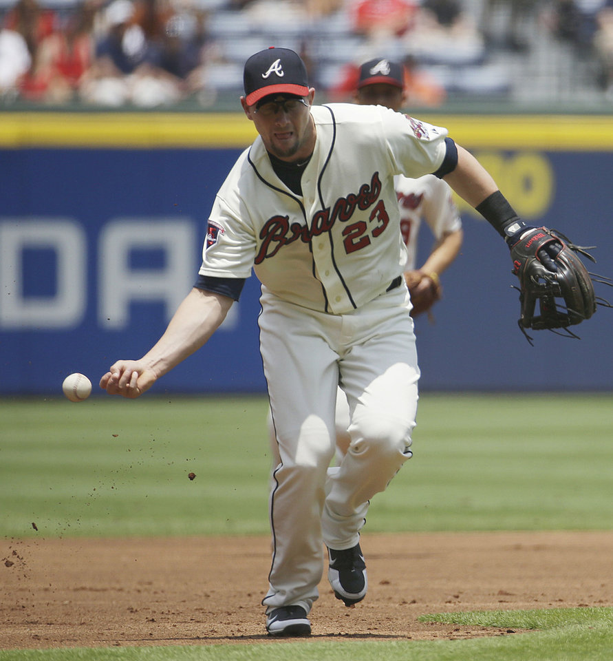 Photo - Atlanta Braves third baseman Chris Johnson misses the ball while fielding a soft ground ball in the first inning of a baseball game, Sunday, July 6, 2014, in Atlanta. (AP Photo/David Goldman)