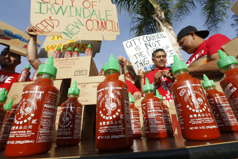 Photo - Sriracha hot sauce bottles are set by supporters protesting ahead of the city council meeting in Irwindale, Calif., Wednesday, April 23, 2014. The Irwindale City Council has declared that the factory that produces the popular Sriracha hot sauce is a public nuisance. (AP Photo/Damian Dovarganes)