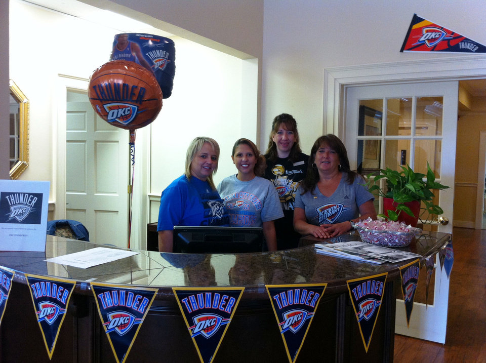 Photo - From left, Rhonda Ratliff, Trisha Foster, MaRenda Bedo and Jill O?Neal sport their team colors in the Edmond branch office of Capitol Abstract. PHOTO PROVIDED