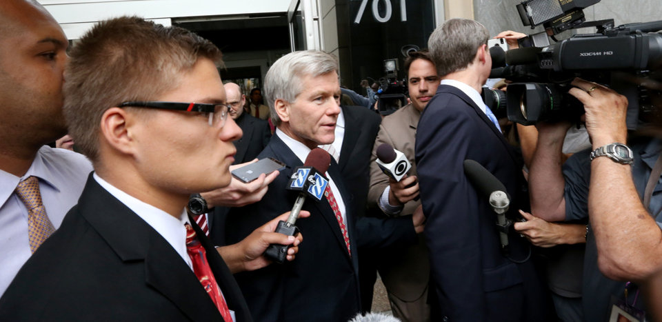 Photo - Former Virginia Gov. Bob McDonnell, center, walks by reporters as he leaves the Federal Courthouse in Richmond, Va., Tuesday, July 29, 2014. McDonnell and his wife are charged in a 14-count indictment with accepting more than $165,000 in loans, designer clothes, vacations and a Rolex watch from Jonnie Williams, the CEO of dietary supplements maker Star Scientific. (AP Photo/Richmond Times-Dispatch, Bob Brown)
