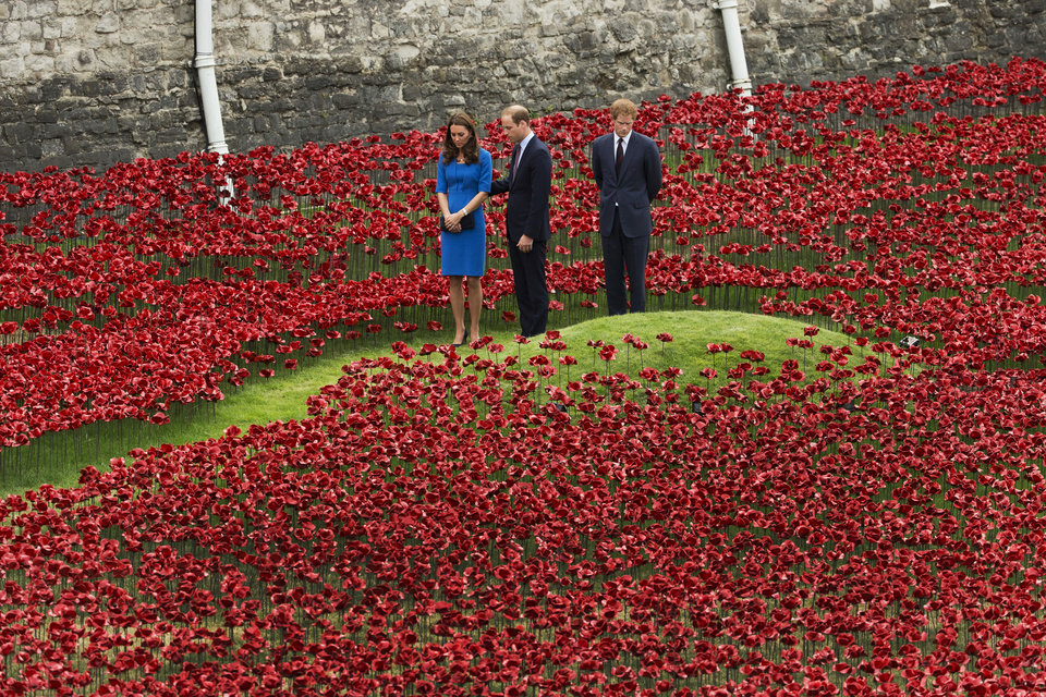 Photo - AP10ThingsToSee - Britain's Duke of Cambridge Prince William, center, his wife Kate the Duchess of Cambridge and his brother Prince Harry visit a ceramic poppy art installation by ceramic artist Paul Cummins entitled 'Blood Swept Lands and Seas of Red' for its official unveiling in the dry moat of the Tower of London in London, Tuesday, Aug. 5, 2014. AP Photo/Matt Dunham)