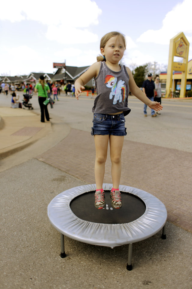 Photo - Kendal Goss, 6, bounces on a mini trampoline at Open Streets OKC, along NW 23rd Street between Robinson and Western, Sunday, March 22, 2015. Photo by Doug Hoke, The Oklahoman