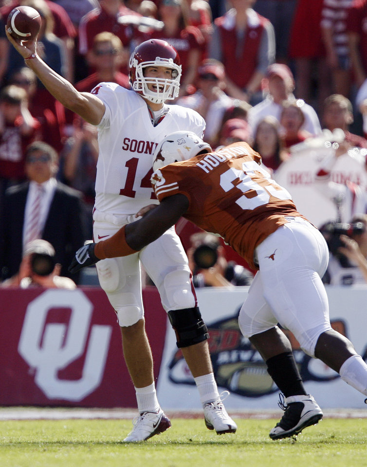 Photo - Oklahoma's Sam Bradford takes a hit on a pass attempt from Texas' Lamarr Houston (33) during the Red River Rivalry college football game between the University of Oklahoma Sooners (OU) and the University of Texas Longhorns (UT) at the Cotton Bowl in Dallas, Texas, Saturday, Oct. 17, 2009. Photo by Chris Landsberger, The Oklahoman