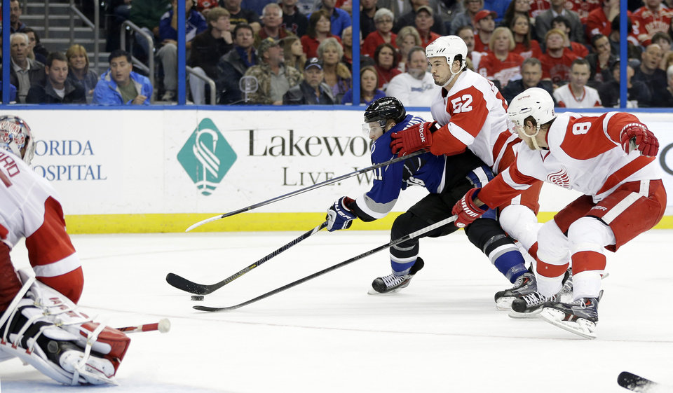 Photo - Tampa Bay Lightning center Tom Pyatt (11) gets past Detroit Red Wings defenseman Jonathan Ericsson (52) and left wing Justin Abdelkader (8) to score on goalie Jimmy Howard (35) during the second period of an NHL hockey game Saturday, Feb. 8, 2014, in Tampa, Fla. (AP Photo/Chris O'Meara)